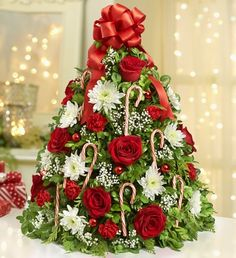 Deck the halls with our Holiday Flower Tree® including fragrant cedar and boxwood adorned with red roses, candy canes, mini carnations and more, in the shape of a traditional Christmas tree! Starting at $59.99.