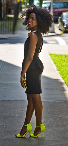 Fashion Alert: Say Bye To Boring Black. African-American fashion model wearing black dress, gold accessories and neon green high-heel pumps
