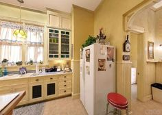 Charmed Halliwell Manor kitchen has always been my favorite style of kitchen with its large, open space, a farmhouse butcher-block Island, and the pièce de résistance are the Queen Anne stained glass window cabinets I even love the yellow and white.