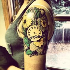 Tattoo with a clock and flowers. Beautifull !