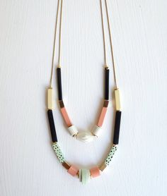 """Kibo is one of the necklaces for Après Ski new collection """"Our Garden Needs Its Flowers"""". This is inspired by Memphis Milano, a movement of architecture and industrial design in the 80, Art Deco and Africanism are also influences, all mixed with the subtlety of color and geometric shapes typical from Après Ski. Kibo stands out for the inclusion of black glass cylinders, which are vintage pieces."""