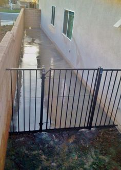 Dog run on side of house with powder coated metal gate/fence pannel. Drains on center spaced out approx. 8' appart to hose down slab or water runn off.