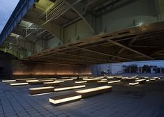 An outdoor wooden performance space is sheltered by the bridge and includes illuminated benches made of artificial stone and wood.