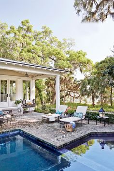 A patio with a black-bottomed lap pool and hot tub at the heart of the compound, between the main house and guest accommodations. The flooring is Savannah Grey bricks, an antique variety with mortar handmade from ground oyster shells.