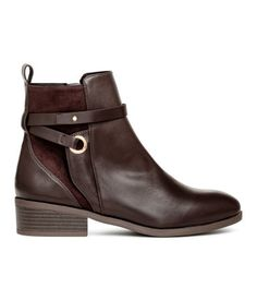 Dark brown. Ankle boots in faux leather with details in faux suede. Loop at back, decorative straps, and side zip. Fabric lining, faux leather insoles, and