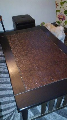 My DIY Faux Leather inlay Coffee Table project. Started out as a White painted table. I distressed the fabric that was a light brown faux leather by dying it with crimson red, burnished brown and black paint, painted the table with black acrylics, attached the fabric with spray adhesive then Polyurithaned it to age the fabric and protect the table. Last step was adding the antique pewter grauments.