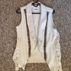 buckle vest floral/lacy sides with tribal print running down both sides of the front. Great with a tank top, short sleeve or long sleeves underneath. May have been worn once. Light creams color Buckle Tops