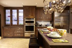 Kitchen By: Christopher Peacock. The kitchen is designed with oak cabinetry, a wooden oven hood, and leather-backed hardware.