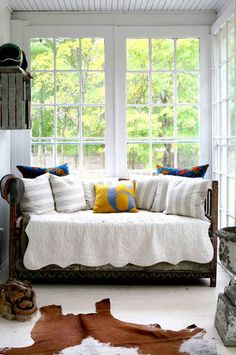 hamptons home of bob and courtney novogratz. love this cozy little sun porch flooded with natural light and the antique daybed.  bright, airy and fun.