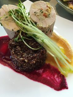 Chicken 2 ways, roulade of chicken stuffed with chicken mousse, goat cheese, roasted red pepper, grilled corn on top of red quinoa cake with sautéed pea shoots and garnished with a red and gold beet sauce