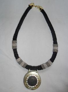 Colar com fio de corda coberto com fitas e miçangas mescladas, medalhão dourado com aplicação de botão forrado e strass. Acabamento dourado. R$ 26,00