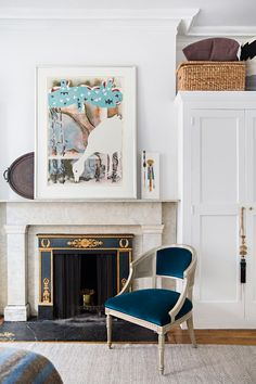 """A chair dressed in a blue velvet from Kravet keeps the bedroom fireplace company. The artwork on the mantel is another Jean-Paul Riopelle creation; tucked behind it is an antique tray from India. """"I don't like going into a shop and finding five, six, seven things,"""" Ouellette explains. """"I'd rather find one object, a particular little thing."""""""