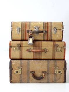 A vintage striped suitcase circa 1920s. The hard case luggage features a golden tan cover with rust red tone striping. It has a rust brown leather trim and a leather handle. Brass tone fixtures and lo