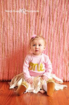 Baby girl's first birthday portraits // Pink and gold // Pink ruffle background, gold sequins, fabric strip skirt, glitter // by Mandy Ringe Photography