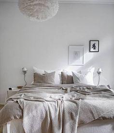 Magnifique chambre décorée dans les tons blanc et beige. L'utilisation des matières naturelles comme les draps en lin ou la suspension en plume apporte une touche très authentique à cette décoration minimaliste. #decoration #deco #bedroom #chambre