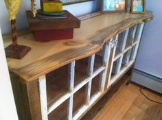 This sideboard was made from reclaimed barn board with a live edge pine top. The doors are old windows and the original window latches were used for door knobs/latches.