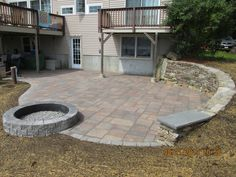 Unilock Beacon Hill Flagstone patio pavers.  Unilock Roman Stack Fire Pit. New England Fieldstone wall.