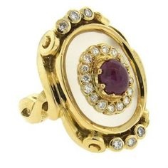 An 18k yellow gold ring, crafted by Ilias Lalaounis, featuring frosted crystal top, 5.7mm x 4.8mm ruby cabochon in the center, surrounded by approx. 0.40ctw in diamonds DESIGNER: Lalaounis MATERIAL: 1
