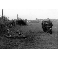 Waffen-SS soldiers of the 1st SS-Panzer Division paying respect to a recently fallen comrade during the fighting near Caen in Normandy.