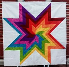 A modern quilt called the Rainbow Swirl Quilt made from half square triangles and squares. Lap Quilts, Scrappy Quilts, Antique Quilts, Vintage Quilts, Rainbow Quilt, Rainbow Swirl, Rainbow Baby, Modern Quilting Designs, History Of Quilting