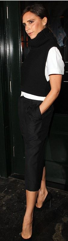 Who made  Victoria Beckham's white button down shirt, black cropped pants, black pumps, and turtleneck sweater vest?