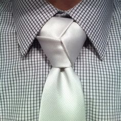 white trinity knot tied over a white and grey pattern shirt #trinity #knot