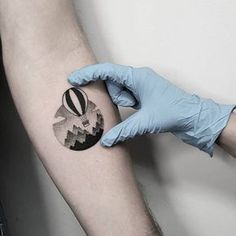 Air ballon landscape circle tattoo on the left inner forearm.
