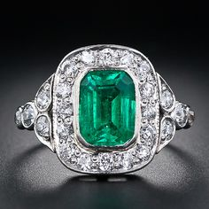 This classic Art Deco ring, handcrafted in platinum circa 1930, features a lovely and lively bright-green Colombian emerald weighing 1.65 carats. The beautiful, bezel-set emerald radiates from within a sparkling frame of colorless European-cut diamonds held aloft by a pair of elegantly designed diamond-set shoulders. An endearing and enduring gem.