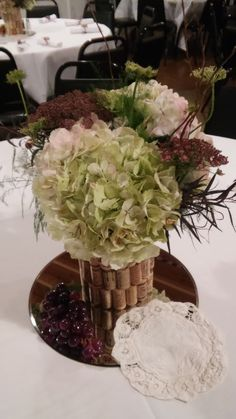 Centerpiece for wine-themed wedding. Antique hydrangea, chocolate lace with wine cork base.