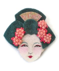PRICE: WAS 20$ NOW 18$    A beautiful felt brooch featuring a Geisha girl which will give an oriental touch to your accessory collection.    This felt brooch is an original design, handcrafted using a combination of ultra suede and felt fabrics. The hair is embellished with lace flowers and embroidery and her face is hand painted with acrylic colors.    This art brooch is backed with a safety pin and measures 5.8 cm high (2.28 inch) and 5.5 cm wide (2.16 inch) and will arrive in a handmade…