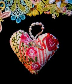 Using a vintage quilt from the 1940's, I cut out heart shaped designs and then embellished each one with Silk ribbon embroidery, dyed laces, charms, beads, sequins, and various tpes of threads. A loop large enough to act as a hanger was made us pearl beads - Nikke Lee