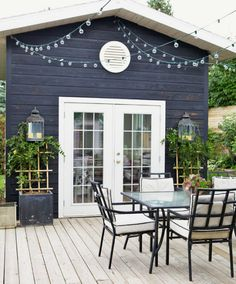 I would love this patio....love the plants and lights flankingn either side of the door and love the string lights