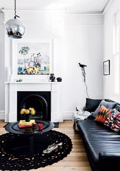 i love this victorian modern space featured on inside out magazine. it's quite dark in terms of that chic black leather sofa paired with a black crochet area rug, the damien hirst skull print and that