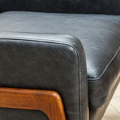 Handsome, sophisticated, and timeless. One can never go wrong with black leather. Wooden Leg, Leather Furniture, Ottoman, Black Leather, Mid Century, Black Chairs, Stylish, Classic, Handsome