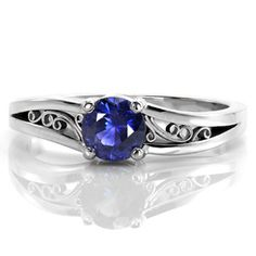 Design 2386 - A 0.60 carat round cut natural blue sapphire is set in a classic four prong setting. Repeating the curves of the center stone, rhythmic scrolls of hand wrought filigree decorate the pockets created by the split shank. Crafted in 14k white gold, the bands unique split creates a soft waved contour.