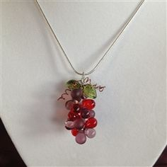 """Grape Cluster Necklace is fashioned from an assortment of grape and wine colored glass teardrop beads on silver jewelry wire and accented with glass grape leaf beads.  Brown jewelry wire replicates a grape vine design to compliment overall authentic appearance.  An 18"""" sterling silver chain completes this handcrafted unique wine jewelry - $19.95"""