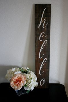 hello  This cute vertical sign is printed with off-white acrylic paint on dark walnut-stained wood. Comes with sawtooth hanger on back, so it