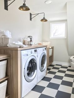 Light and airy laundry room with light white oak cabinets and black and white checkerboard floors