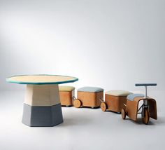 "Smart kids' furniture. The train can be three seats around the table, and the seat of each ""car"" opens to access a large storage space. By KAMKAM."