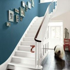 I adore the teal walls with the white wooden staircase.