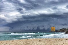 And incredible shelf cloud moves across the sky at Tamarama Beach with an apt 'Beach Closed: No Swimming' sign in place