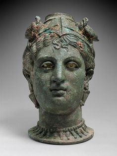 3rd -2nd C. BCE. Balsamarium; a Perfume jar. Likely the Etruscan goddess of love Turan. Or a Lasa, a spirit of beauty who waited on Turan and mortal women at their toilet. A diadem with two doves is linked to worship of Aphrodite. Her eyes likely had glass irises. She wears elongated drop earrings and a necklace. Bronze, found in a tomb in Etruria. Etruscan.