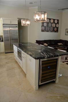 Kitchen Island by Kitchen Designs & More with white cabinets, black & white granite countertop, stainless steel wine fridge and microwave in drawer cabinet,