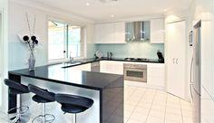 Kitchen: Glossy White cabinets, black quartz bench top, blue tinted glass splash back.