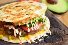 This is one amazing burger, a cheeseburger and a quesadilla in one. Juicy burger in between two cheese-covered, crispy flour tortillas topped with corn, tomatoes, fresh jalapeno peppers, avocado and chipotle mayo.