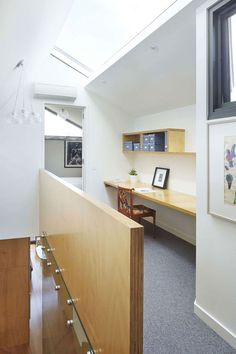 Interior Design Idea - 13 Examples Of Desks In Hallways // A long floating desk with a narrower shelf above it has turned this hallway into a functional workspace, and the space is kept bright by the skylight above.