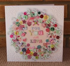 'For You With Love' handmade card featuring a wreath made of buttons, bows, ribbon, hearts and flowers.