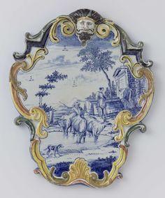 Anonymous | Plaat in de vorm van een cartouche met mascaron; beschilderde in blauw met een landschap met koeien, Anonymous, c. 1750 - c. 1780 | Plaat in de vorm van een cartouche met mascaron; beschilderde in blauw met een landschap met koeien. Rand veelkleurig.