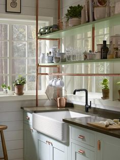 A wide white farmhouse sink paired with a Kohler oil-rubbed bronze faucet is mounted above light blue cabinets accented with bronze cabinet pulls and a gray quartz countertop mounted beneath light blue shelves placed on bronze pipes in front of a window.