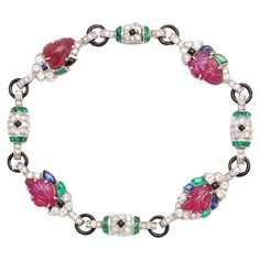Art Deco Tutti Frutti Bracelet. Sapphire, diamond, emerald, and carved ruby bracelet, set in platinum with black enamel links.  American, ca. 1930.